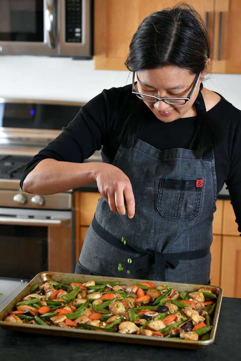 An Asian woman is sprinkling sliced scallions on a sheet pan filled with stir-fry chicken and vegetables.