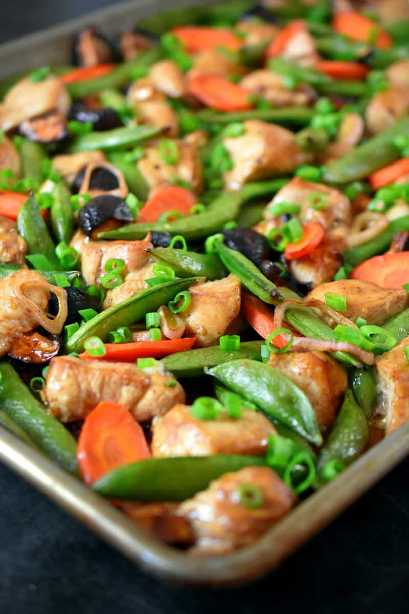 A side view of a sheet pan chicken stir fry dinner right out of the oven, topped with scallions