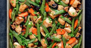 An overhead shot of sheet pan chicken stir-fry right out of the oven. Two hands are holding the edges of the pan with blue and white towels.
