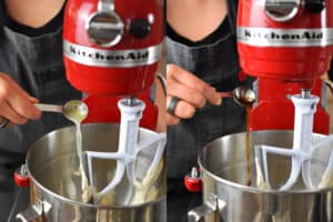 A closeup of someone adding spoonfuls of lemon juice and vanilla extract into a red KitchenAid stand mixer