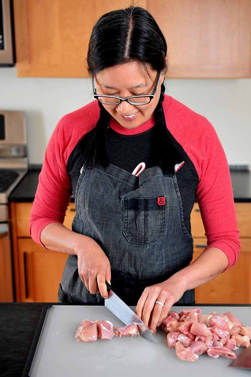 An Asian woman in a gray apron and red and black shirt is cutting boneless, skinless chicken thighs into uniform pieces.