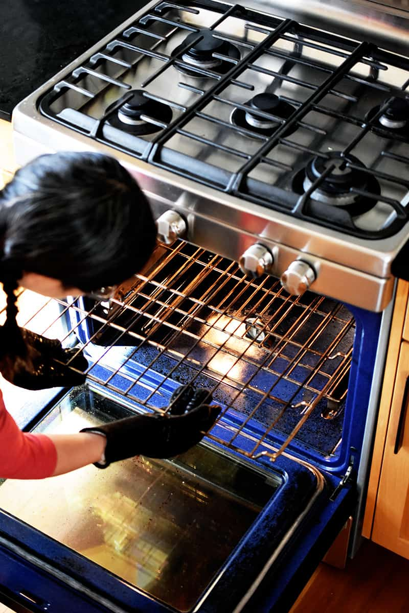 An Asian woman with braids is rearranging her oven rack to be 6 inches from the broiler.
