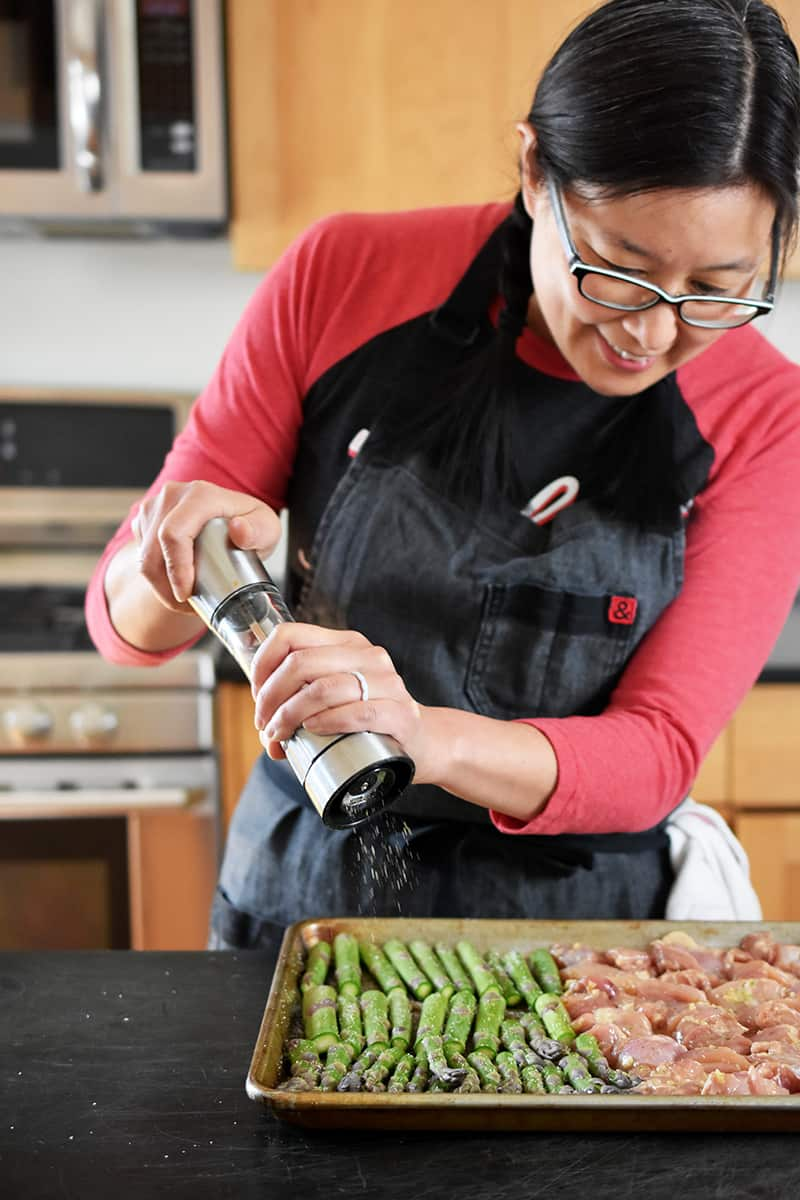An Asian woman is adding freshly ground black pepper from a pepper mill onto some asparagus on a sheet pan.