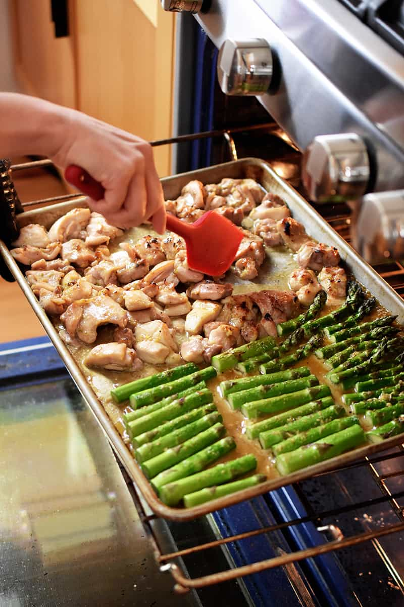 An open oven where someone is using a red silicone spatula to stir sheet pan chicken and asparagus at the halfway point.