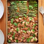 An overhead shot of sheet pan chicken and asparagus on a wooden table, next to bowls of cauliflower rice, plates, and forks.