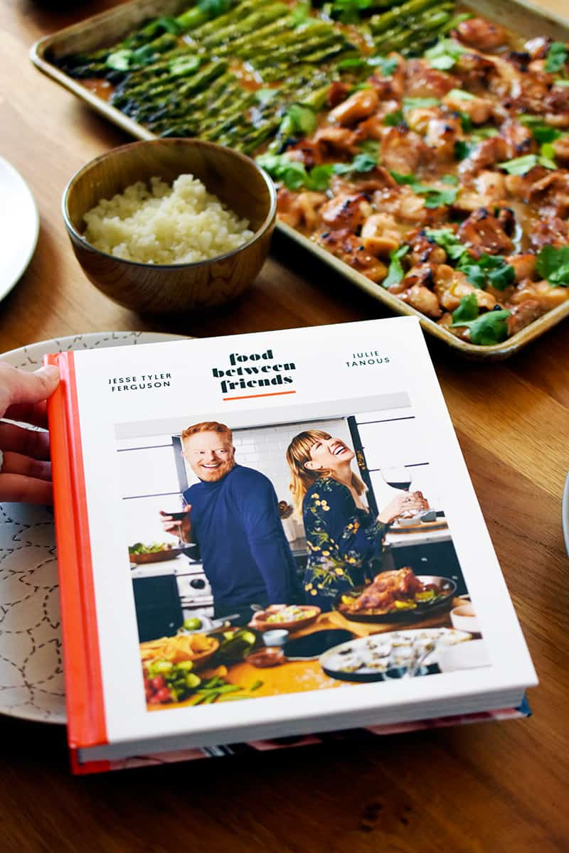 A hardcover copy of Food Between Friends cookbook is next to a Sheet Pan Chicken and Asparagus and a bowl of cauliflower rice.