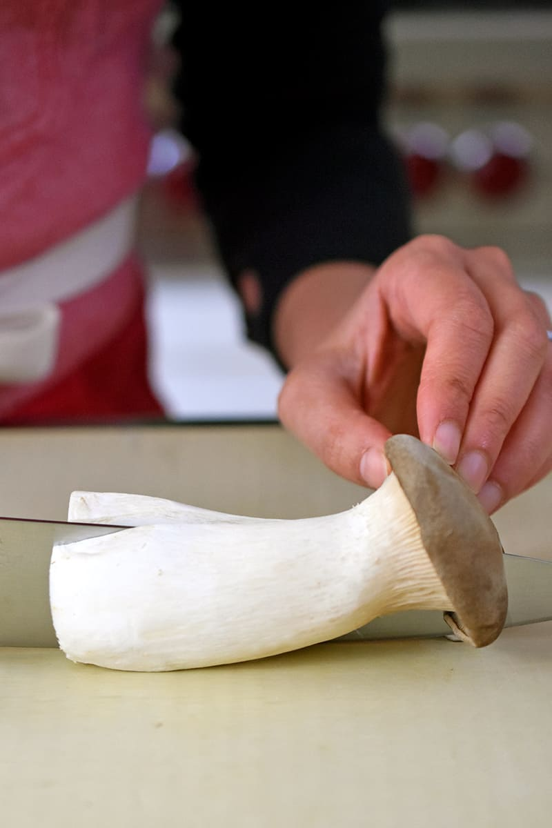 Someone using a chef's knife to slice a king oyster mushroom in half lengthwise.