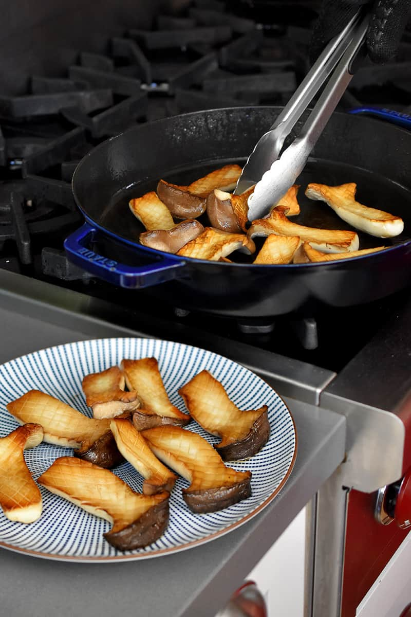 A blue and white plate has golden brown halved king oyster mushrooms and a pair of tongs are transferring the rest from a large frying pan.
