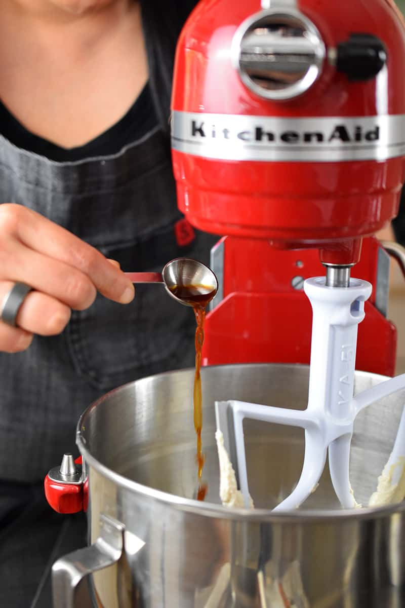 Someone in a gray apron is adding a spoonful of vanilla extract into a red Kitchenaid stand mixer.
