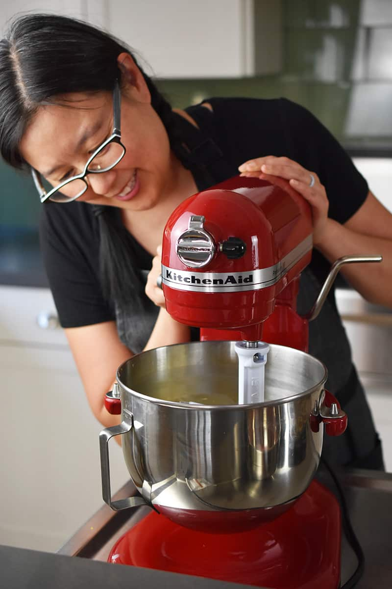A smiling Asian woman is blending strawberry muffin batter in a red KitchenAid stand mixer.