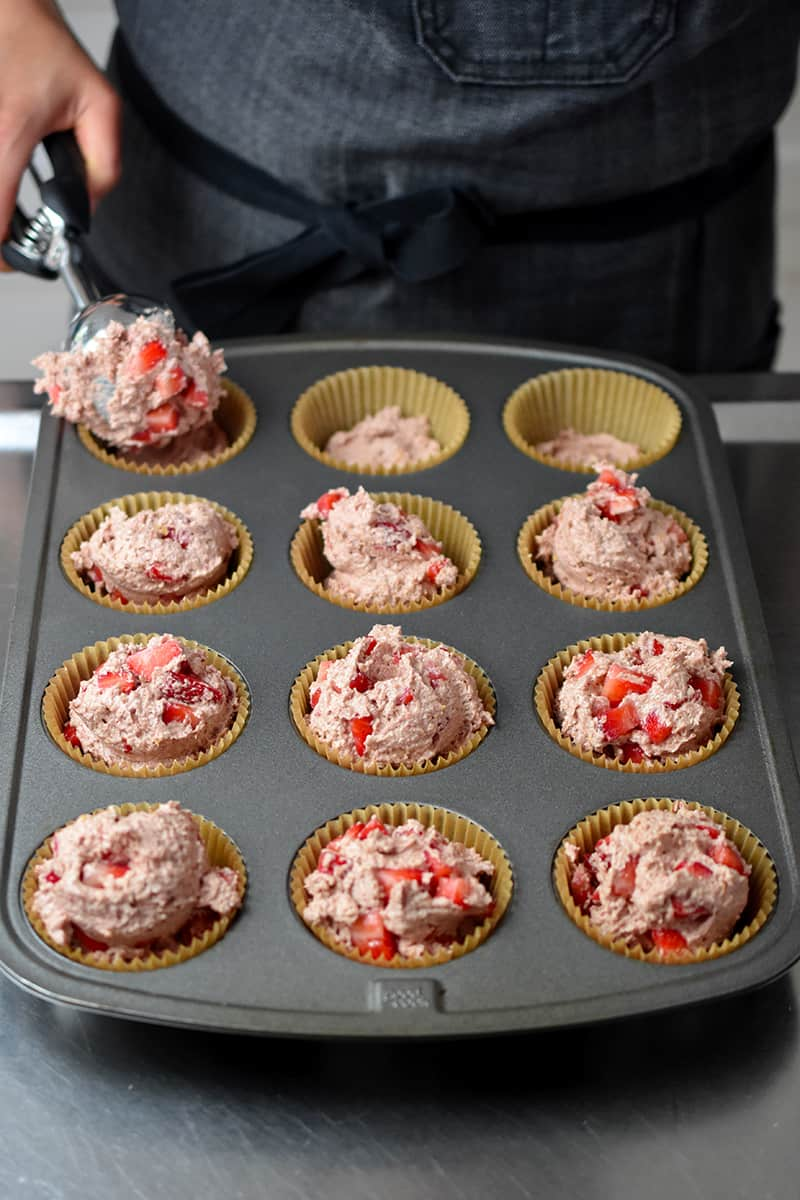 Adding scoops of strawberry muffin batter to a muffin tin that already has some batter on the bottom of the liners.