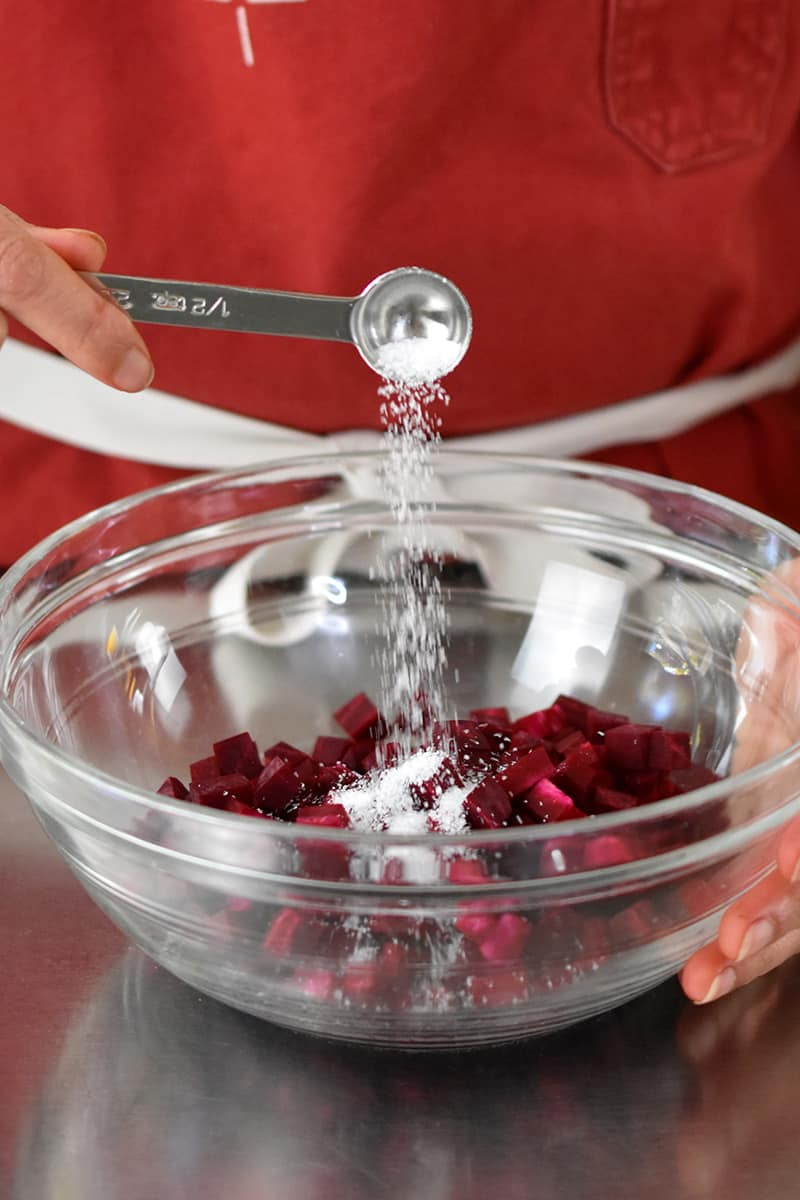 Someone in a red apron is adding a spoonful of salt to a clear bowl filled with diced purple beets
