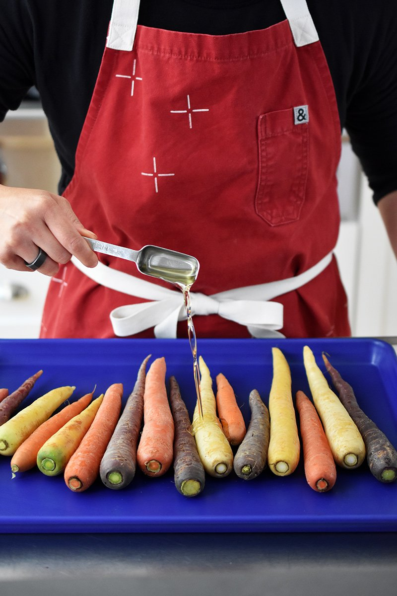 A person in a red apron is drizzling avocado oil on a rimmed baking sheet filled with colorful carrots.