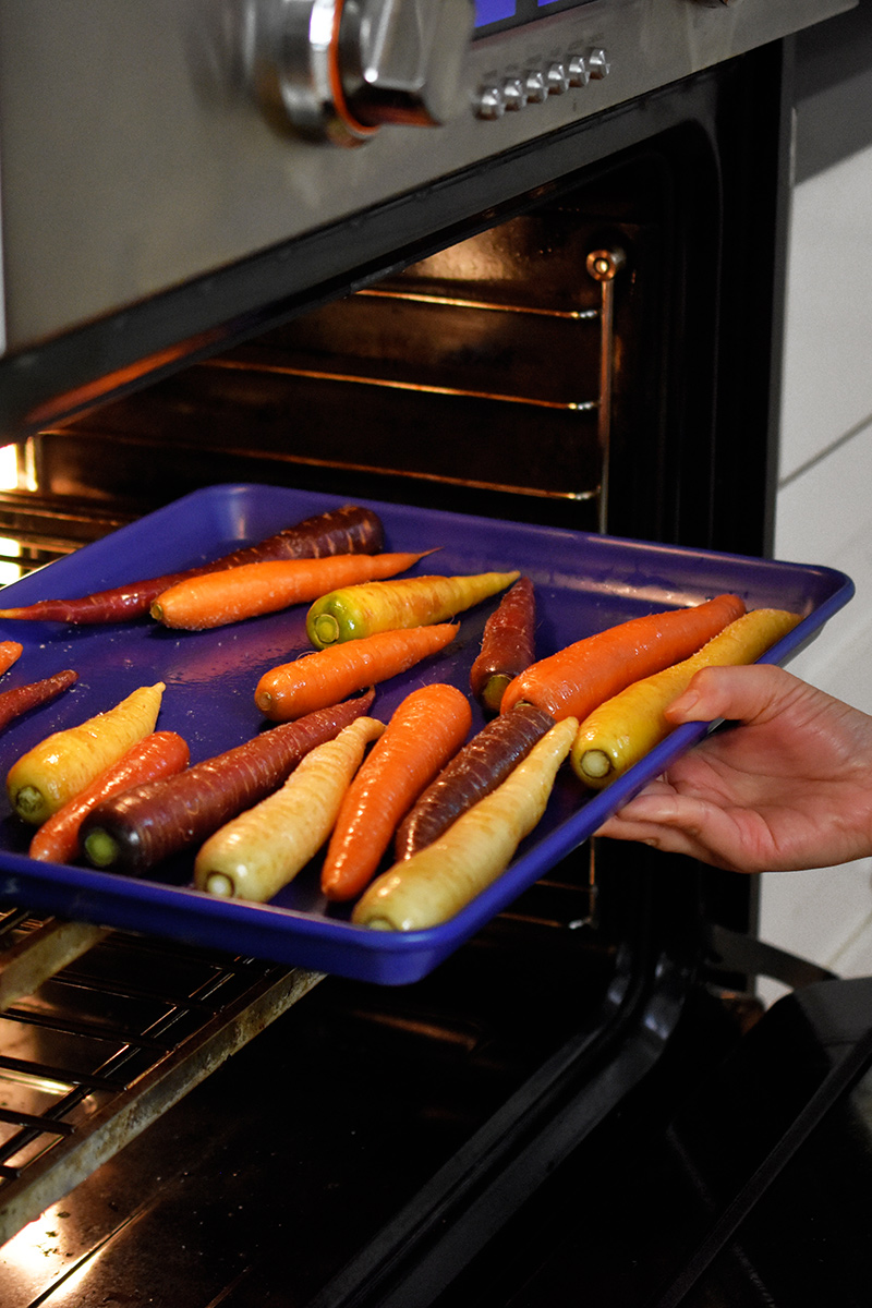Someone putting a blue rimmed baking sheet filled with rainbow colored carrots into an open oven.