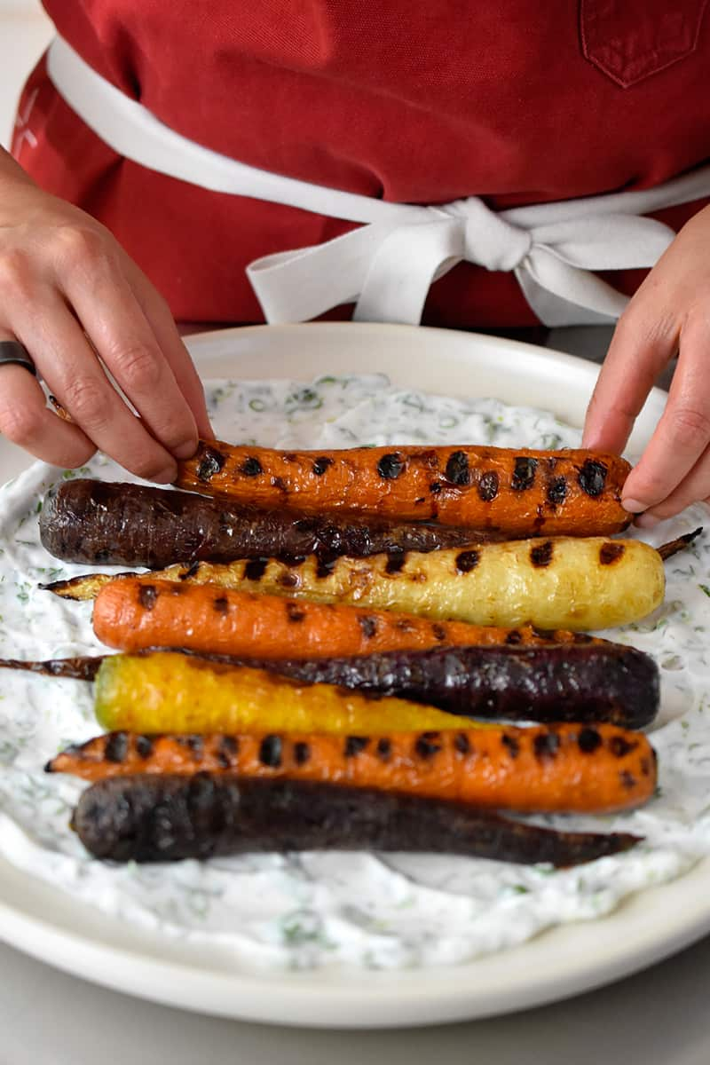 Two hands are placing grilled carrots on a platter with herbed coconut yogurt spread on the bottom.