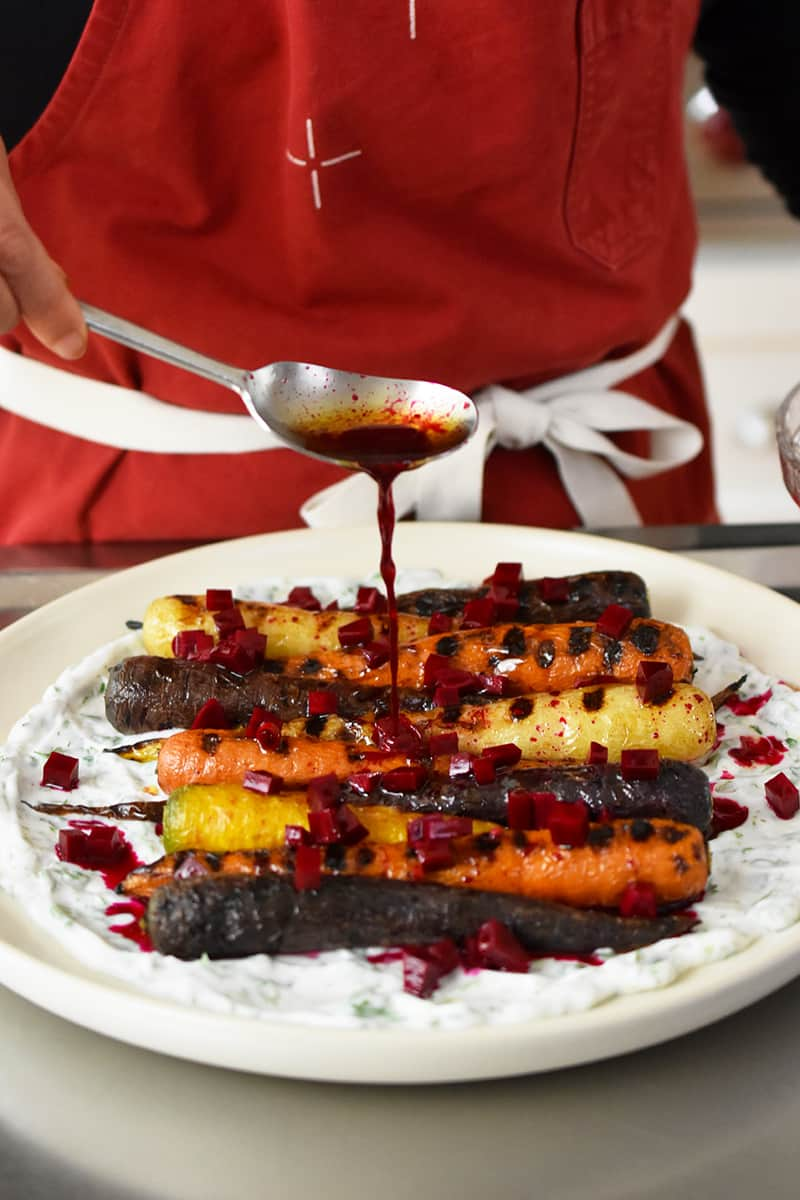 Someone in a red apron is adding beet vinaigrette on top of grilled carrots on coconut yogurt.