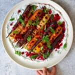 A hand is holding a round platter filled with grilled carrots with herby coconut yogurt and spicy beet vinaigrette