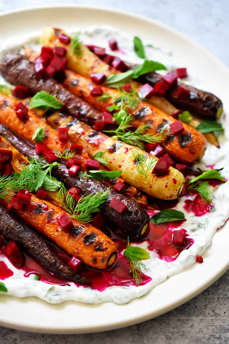 A closeup side shot of Grilled Carrots with Herby Coconut Yogurt and a spicy beet vinaigrette