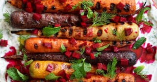 An overhead shot of grilled carrots with herby coconut yogurt and spicy beet vinaigrette.