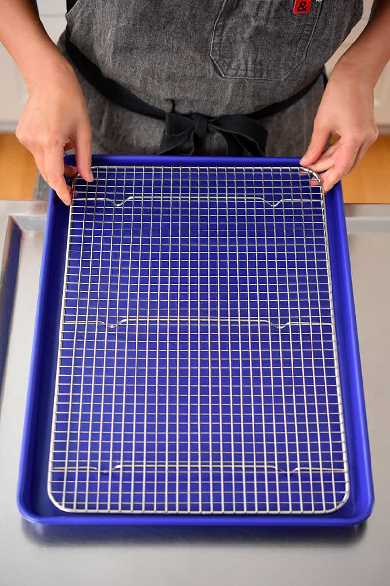 Two hands are placing a wire cooling rack inside a blue rimmed baking sheet.