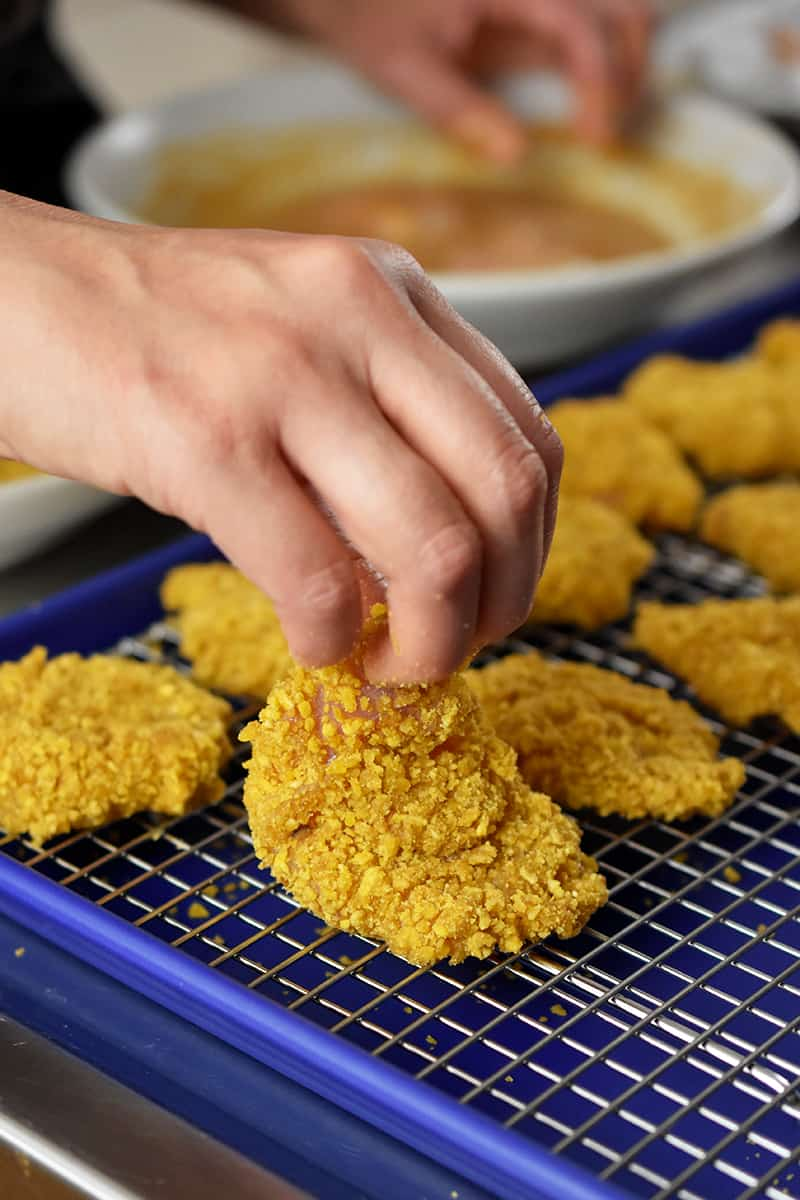 A hand is placing chicken nuggets ready to be cooked in the air fryer in a wire rack in a rimmed baking sheet.