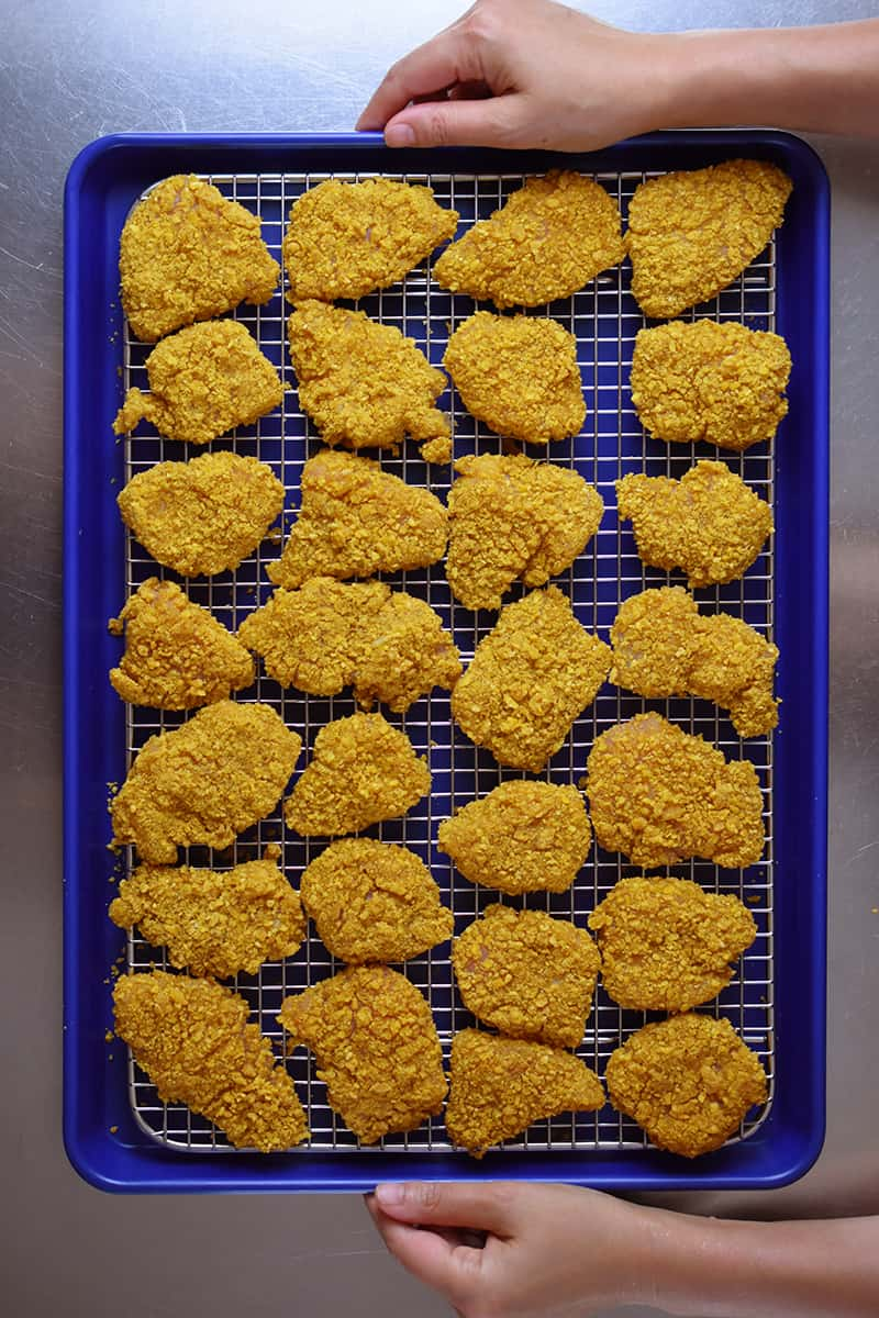 Two hands are holding a tray of air fryer chicken nuggets