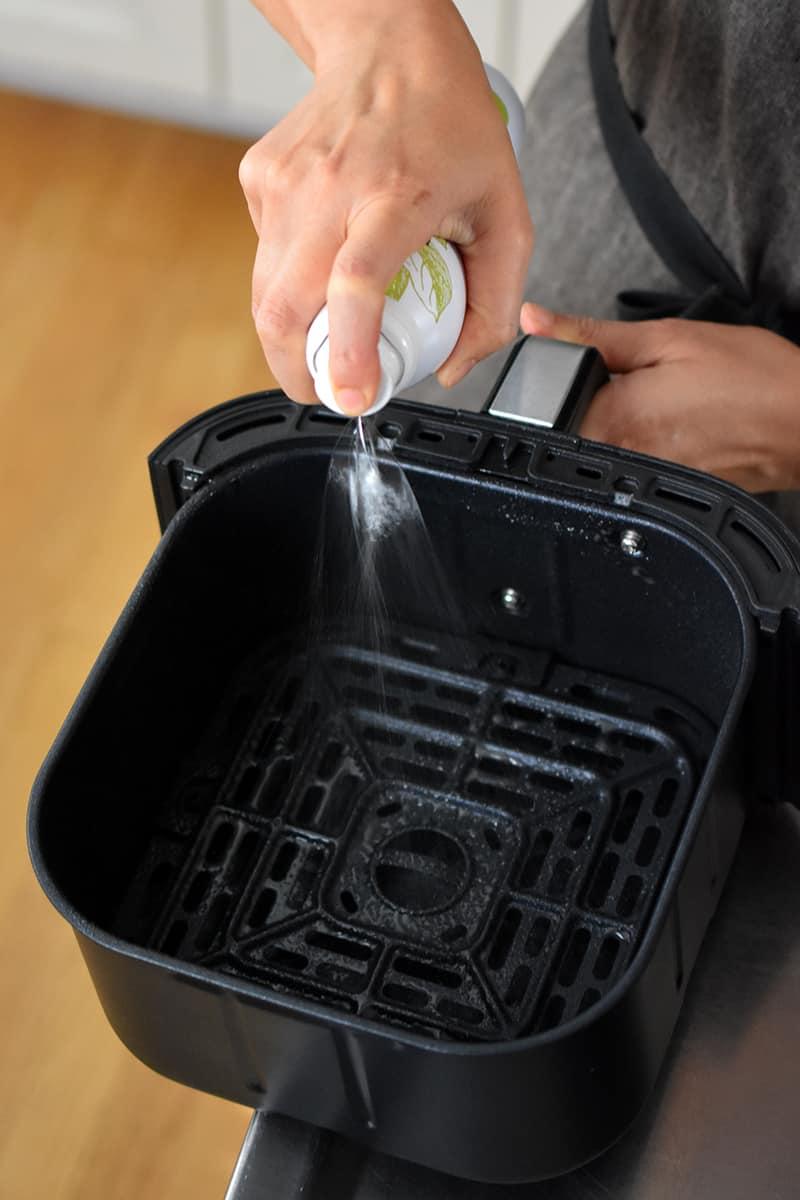 Spraying an empty air fryer basket with avocado oil spray.