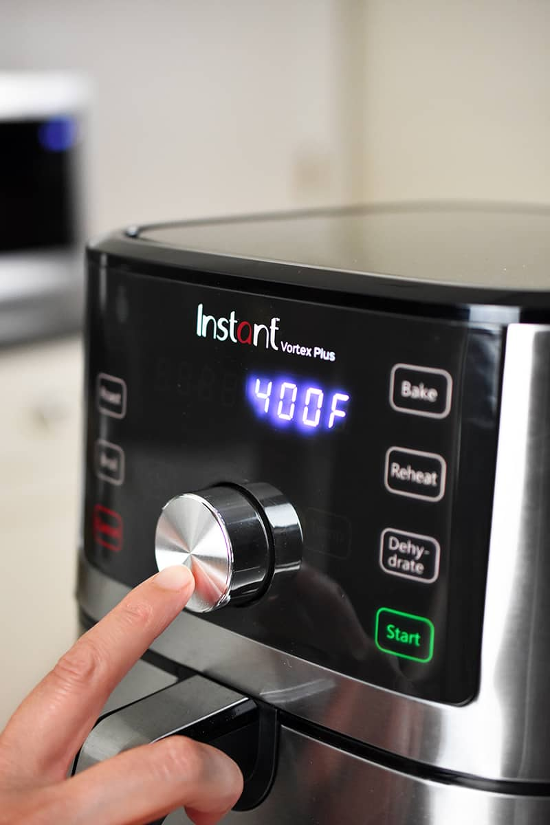 A hand is pushing buttons on an Instant Pot air fryer.