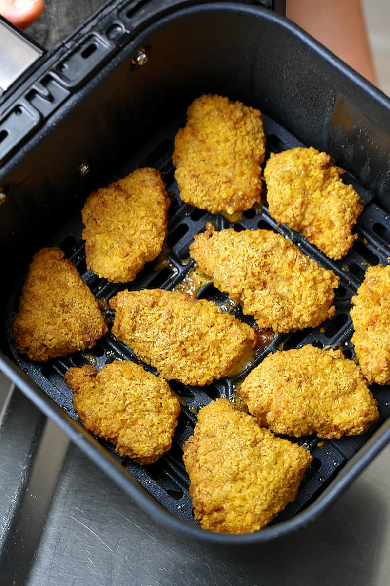 A diagonal overhead view of an open air fryer basket filled with homemade chicken nuggets