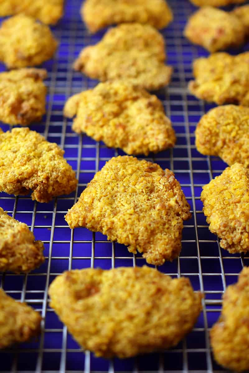 Close-up of air fryer chicken nuggets on a cooling rack in a rimmed baking sheet right after they're finished cooking
