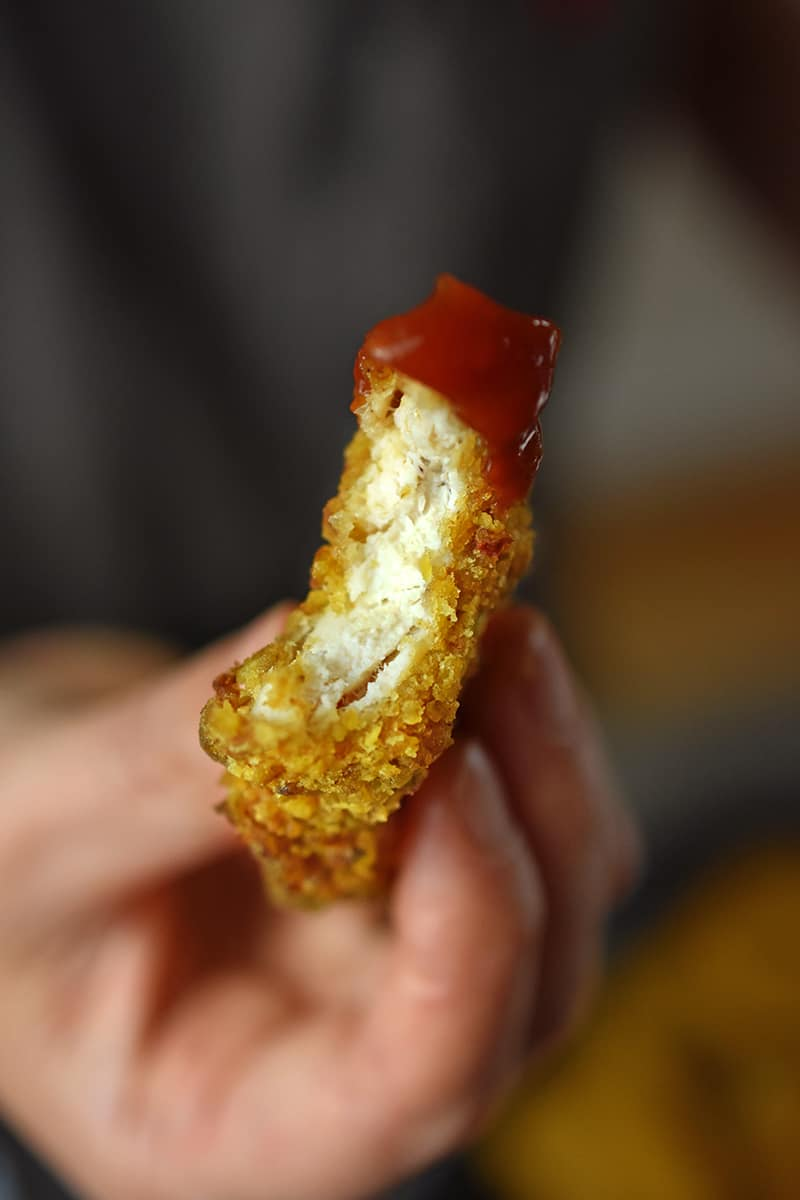 A close up of a chicken nugget dipped in paleo ketchup that has a bite from it.